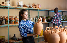 Portrait Of Cheerful Male And Female Artisans Demonstrating Earthenware In Pottery Workshop