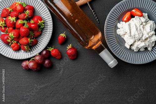 Obraz Bottle of wine with fresh strawberries on black surface - fototapety do salonu