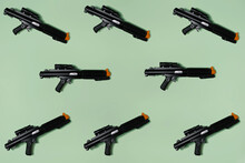 Pattern Created Of Black Rifle Toys. A Top View With Pastel Green Background.