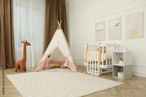 Cute baby room interior with crib and play tent