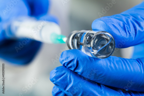 Photographie COVID-19 UK vaccine clinical trial concept,hands in blue gloves holding bottle v