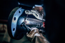 Worker Welding Metal In Manufacturing Plant