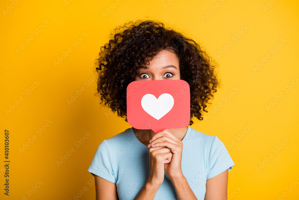 Fototapeta Photo of funky playful dark skin curly girl dressed blue t-shirt holding heart like card cover face isolated yellow color background