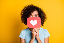Photo Of Funky Playful Dark Skin Curly Girl Dressed Blue T-shirt Holding Heart Like Card Cover Face Isolated Yellow Color Background