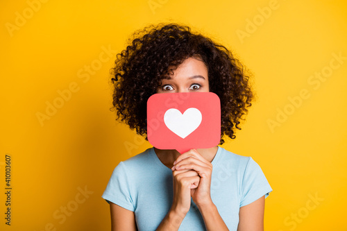 Obraz Photo of funky playful dark skin curly girl dressed blue t-shirt holding heart like card cover face isolated yellow color background - fototapety do salonu
