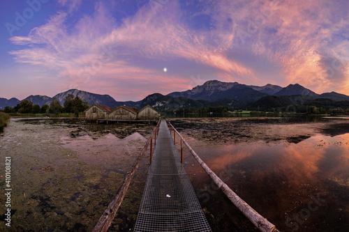 Bootshäuser am Kochelsee mit dramatischen Sonnenuntergang Fototapete