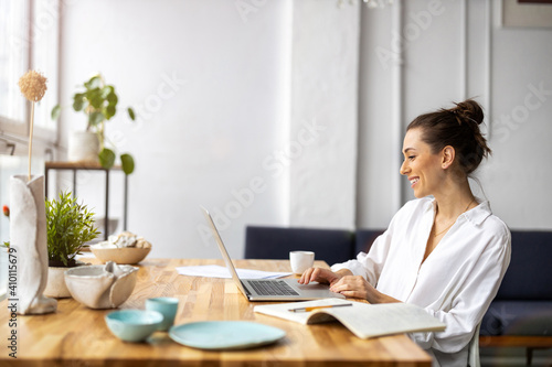 Creative young woman working on laptop in her studio