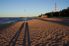 People Are Making Photograph Of Their Shadow At The Sandy Beach With Lighthouse.