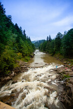 A Fast Mountainous Shallow River Rushes Over The Stones Among The Mountains, Forests And Green Landscapes. There Are Tourist Trails Of The Carpathians