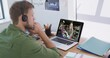 Caucasian man using laptop and phone headset on video call with female colleague