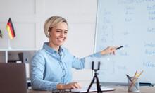 Online Languages School. Female Tutor Giving German Lesson On Internet, Using Smartphone, Explaining Grammar To Students