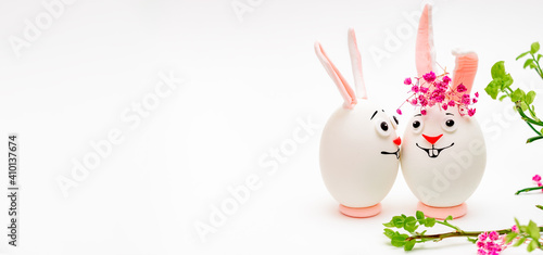Obraz Creative Easter bunnies made of eggs with funny faces painted on them.White background,fresh flowers.Happy Easter concept.Copy space for text. - fototapety do salonu