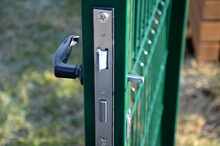 Torn Door Handle On A Metal Green Gate To The Garden. Danger Of Closing And Not Getting Out. Vandalism Of Young