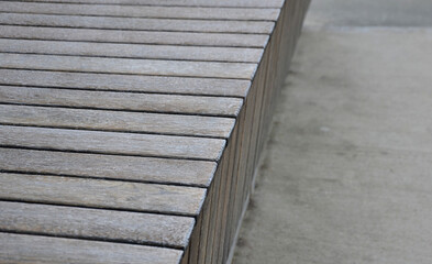 wooden frosted bench made of paneled planks in the shape of a block. in stripes stacked oak gray natural wood covered with hoarfrost in winter