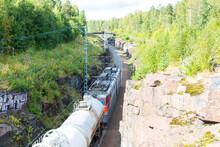 Freight Train Traveling Between Rocks