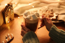 Woman Holding Cup Of Hot Drink With Marshmallows At Wooden Table, Closeup. Magic Christmas Atmosphere