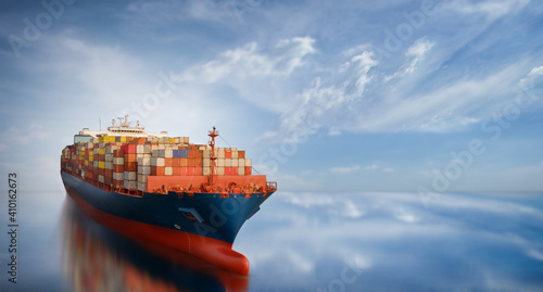Fotografie, Obraz Aerial side view of smart cargo ship carrying container from custom container depot go to ocean concept freight shipping by ship service on blue sky background
