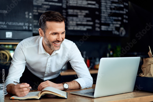 Fototapeta Happy cafe restaurant owner using laptop writing expenses. Small business concept. obraz