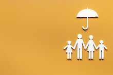Wooden Family Figure Under Umbrella With Space For Text. Insurance Concept