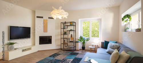 Obraz Panorama of wide modern living room with design sofa and large pillows above. Design library and small fireplace - fototapety do salonu