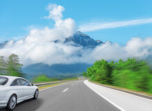 A White Car Rushes Along The Road Against The Backdrop Of A Beautiful Countryside Landscape.