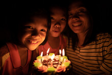 Kids In Family And Cake For Happy Birthday Party On Night, Mother And Children Smiling And Holding Cake And Candles Burning Fire Flame For Birthday Party Friendship Family On Evening Event, Hapy Party