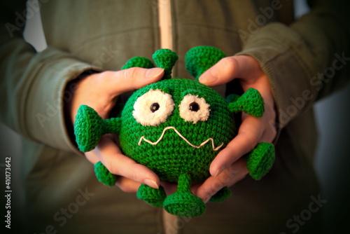 coronavirus toy holdin by hands © Iliya Mitskavets