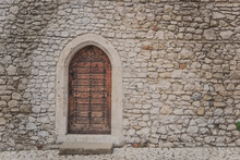 Ancient Wooden Arcade Door With Iron Rivets At Wall Of Old Building. Heavy Closed Door On A Stone Wall Of A Medieval Fortress, Made Of Riveted Wood Planks. Small Back Door To Wawel Castle In Krakow.