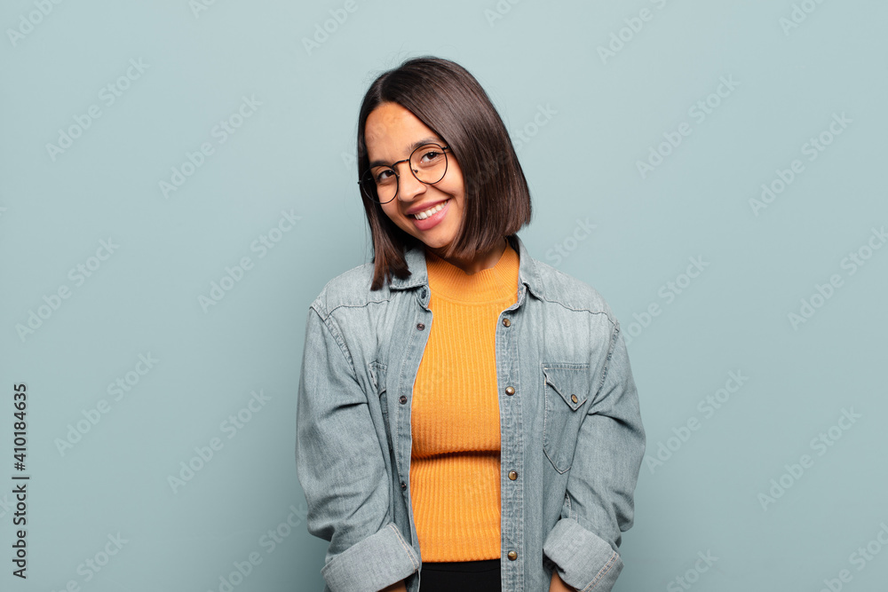 Fototapeta young hispanic woman smiling cheerfully and casually with a positive, happy, confident and relaxed expression