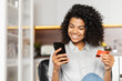 Smiling African American teenage girl with curly hair holding mobile phone, entering credit card number to make an online transaction, mixed-race woman ordering food, doing online shopping from home