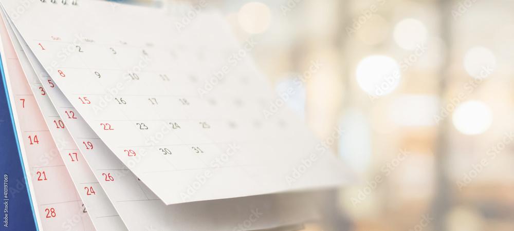 Fototapeta Close up white paper desk calendar with blurred bokeh background appointment and business meeting concept
