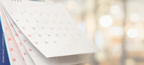 Close up white paper desk calendar with blurred bokeh background appointment and business meeting concept