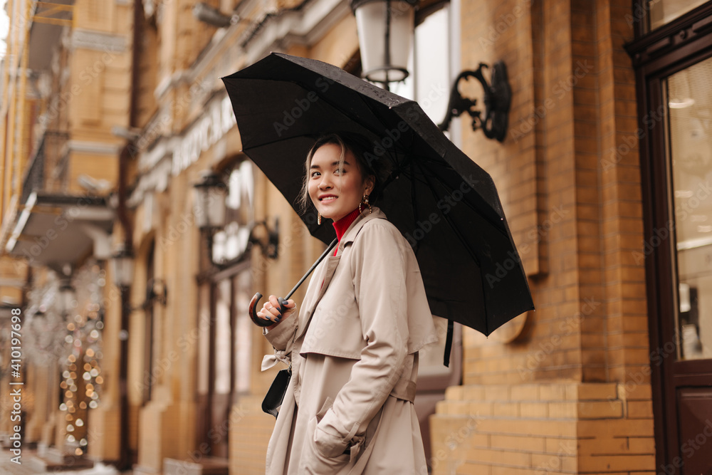 Fototapeta Snapshot of charming Asian girl in stylish trench coat holding black umbrella on city street