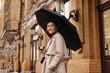 Snapshot of charming Asian girl in stylish trench coat holding black umbrella on city street
