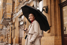 Snapshot Of Charming Asian Girl In Stylish Trench Coat Holding Black Umbrella On City Street