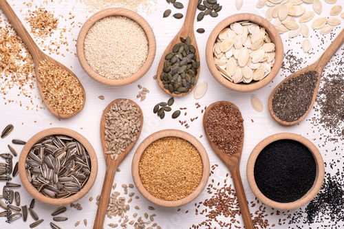 Fotografie, Obraz Healthy seeds - sesame, flax seed, sunflower seeds, pumpkin seed, chia and black seed in wooden spoons on a white background