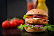 canvas print picture - Big sandwich - hamburger with juicy chicken burger, cheese, tomato, and red onion on black background