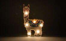 Smiling Llama With Green Accents And Colored Balls Referencing Christmas Illuminated By Six Small Led Lamps. Hearts Around The Eyes And A Calm Countenance. Decorative Object For Baby Rooms.