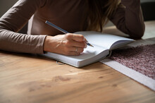 Closeup View Of A Woman Writing In Blank Notebook
