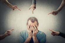 Ashamed Middle Aged Man, Covers His Face With Hands, As Multiple People Points Fingers To Him, Blaming And Scolding. Male Senior Suffering Emotional Breakdown And Depression, Being Under Pressure