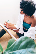 Beautiful Black Woman Artist Painting On Canvas At Home