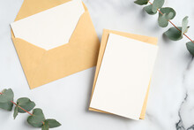 Craft Paper Envelopes With Blank Greeting Cards Mockups And Eucalyptus Leaves On Marble Table. Flat Lay, Top View.