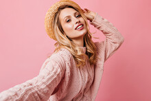 Girl In Boater And Sweater Takes Selfie On Pink Background. Portrait Of Blonde With Snow-white Smile