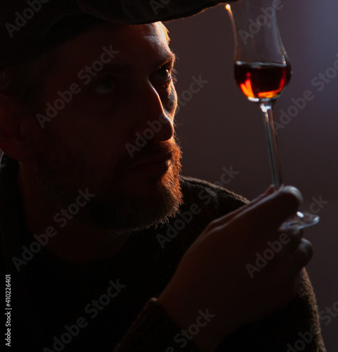 Fotografie, Obraz Man holds glass of sherry in front of him