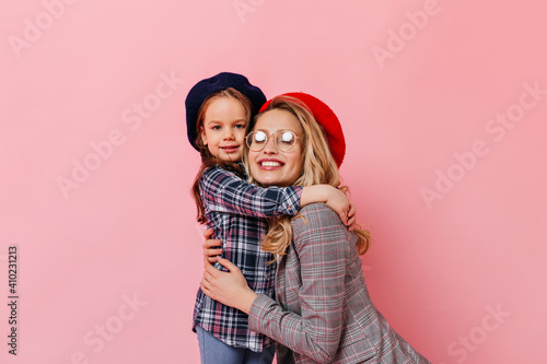 Female child hugs her mother on pink background Fototapet