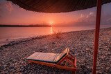 Fototapeta Kawa jest smaczna - Sunset in pink shades with sunbed and parasol on the beach and Mountain Tahtali in the background. Tourism and recreation in the resort of Tekirova and Kemer in Turkey