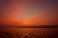 Sunrise From Catamaran Yacht Over The Sea With Mountains In The Background In Sicily. Low Light Photo Of Sunrise Over The Mediterranean Sea.