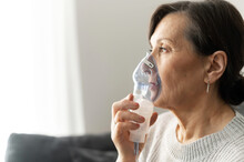 Side View A Senior Older Woman Is Using Inhaler For Flu And Cold Treatment Sitting On The Sofa At Home. Healthcare And Medicine Concept