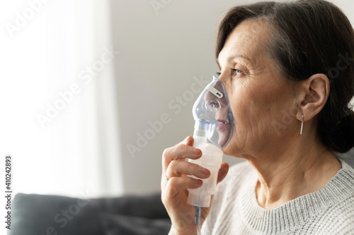 Fotografia Side view a senior older woman is using inhaler for flu and cold treatment sitting on the sofa at home