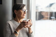 Leinwandbild Motiv Close-up portrait of senior older woman wearing glasses enjoys morning coffee in the kitchen at home. A modern retirement lady daydreaming with a mug of hot drink looks through the window